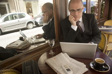 Mature businessman sitting at cafe table looking at laptop