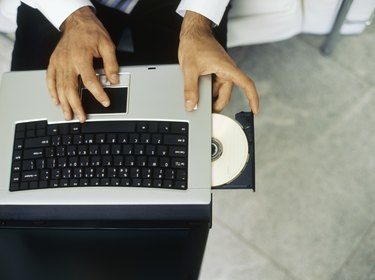High angle view of a businessman inserting a cd into a laptop