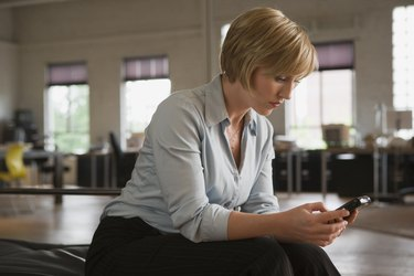 Woman text messaging on cellular phone