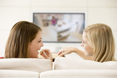 Two women in living room watching television eating chocolates
