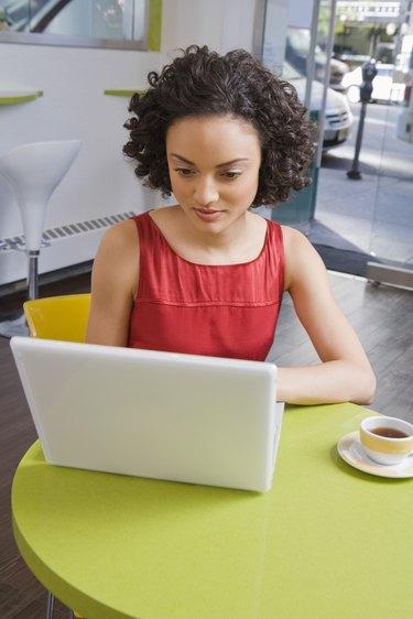 Woman using laptop at cafe