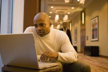 African businessman working on laptop in corridor