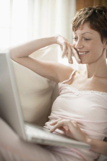Woman using laptop computer on sofa