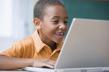 Grinning African boy typing on laptop