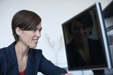 Businesswoman staring at reflection on computer screen