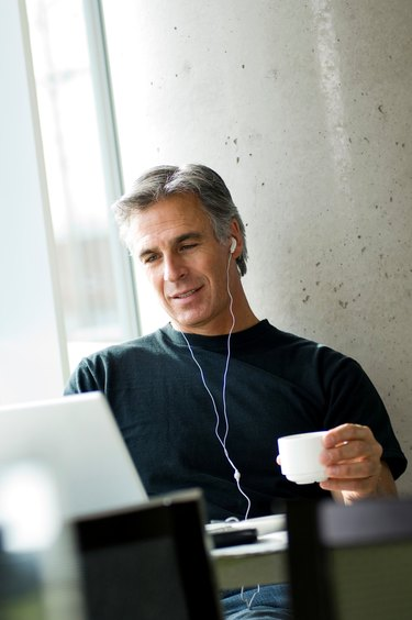 Middle-aged man listening to music in urban cafe.