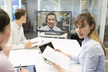 Business meeting in office, chatting on video conference