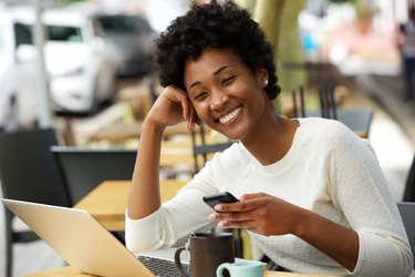 Smiling african woman at cafe with a mobile phone