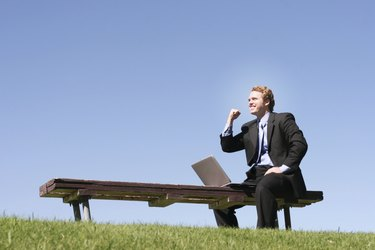 Business man in black suit and blue shirt and tie is holding one arm up in celebration, as he sits on a park bench, next to his laptop