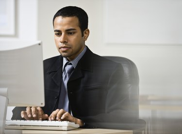 Indian businessman typing on computer