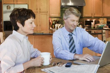 Couple using laptop computer in kitchen