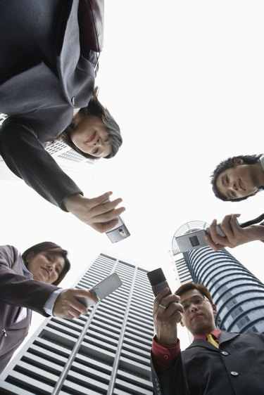 Low angle view of businesspeople with cell phones