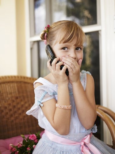 Girl (6-7) using mobile phone, covering mouth with hand