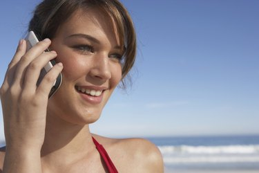 Young woman using mobile phone, outdoors, smiling, close-up