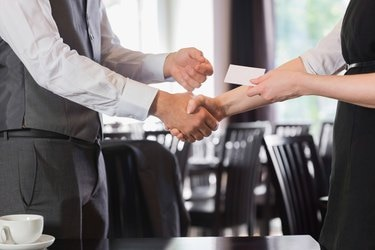 Busines people shaking hands after meeting and changing cards