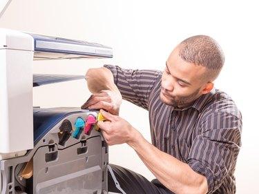african man fixing photo copier