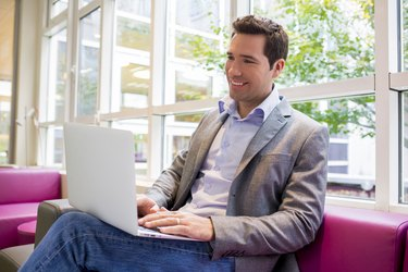Happy smiling young Businessman  working with Laptop on sofa