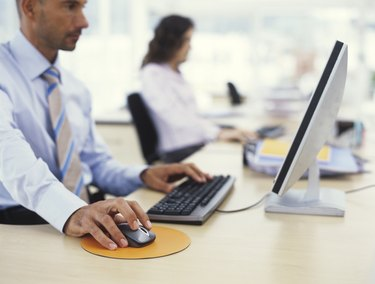 Businessman using PC, hand on mouse, side view