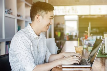 Handsome Asian man with computer in cafe (focus on face)