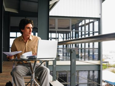 Young businessman using laptop sitting at table on balcony