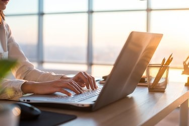 Adult businesswoman working at home using computer, studying business ideas