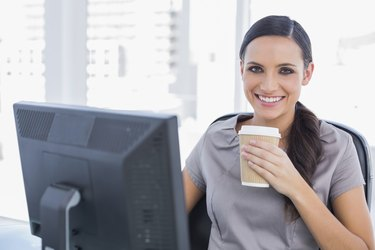 Attractive businesswoman drinking coffee and cheering