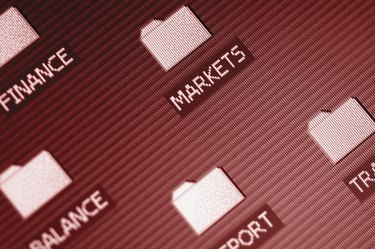 Investment folders on computer desktop, close-up, tilt