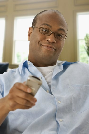 African man watching television with remote control