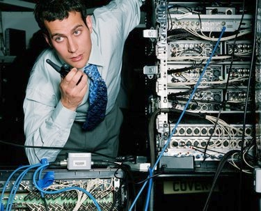 Young businessman using walkie-talkie by servers