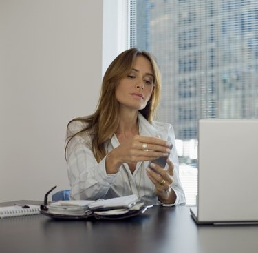 Businesswoman with cell phone in office