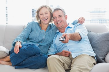 Cheerful couple cuddling and sitting on the couch watching tv