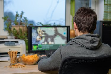 male gamer playing strategy game on computer eating snacks