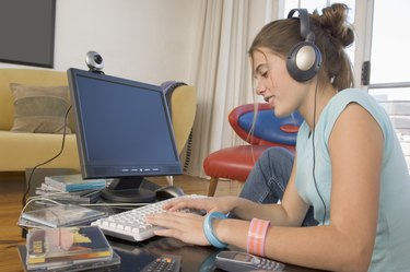 Young woman wearing headphones and using computer