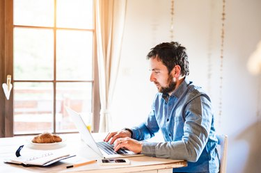 Man sitting at desk working from home on laptop