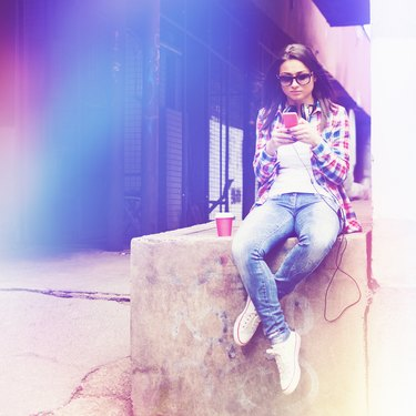 Young hipter woman with smart phone and takeaway coffee