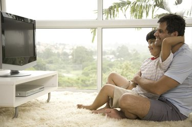Side profile of mature man with his son (8-9) watching television