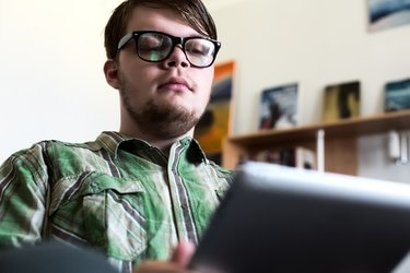 Portrait of Young Man using Tablet Computer in Home Interior