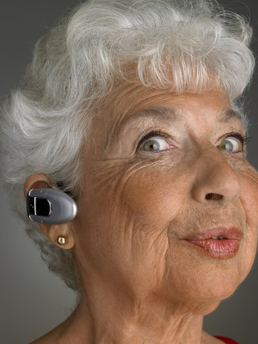 Senior woman wearing bluetooth, pulling facial expression, portrait, close-up
