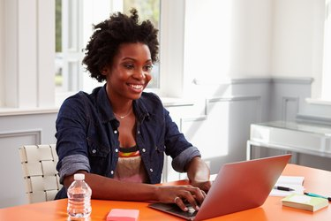 Young black woman using laptop computer at a desk, close-up