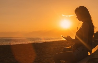 Young woman listen music on the beach