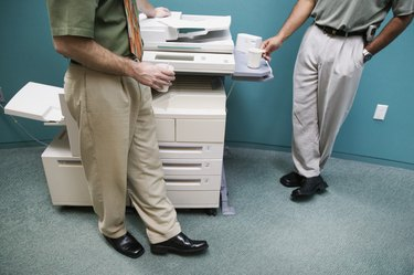Low section view of two businessmen standing at a photocopying machine
