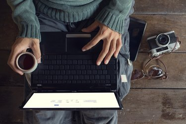 Man hands using Laptop and coffee cup