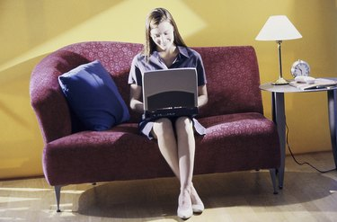Young woman sitting on a couch using a laptop