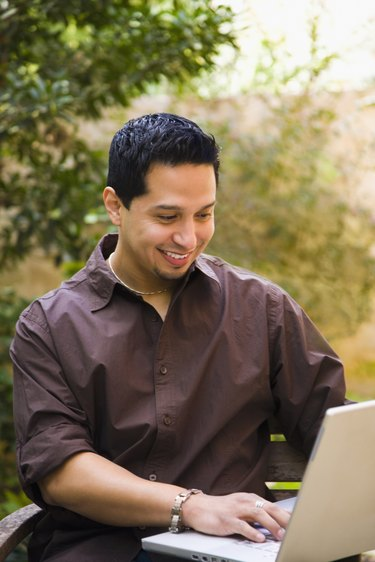Man working on a laptop and smiling
