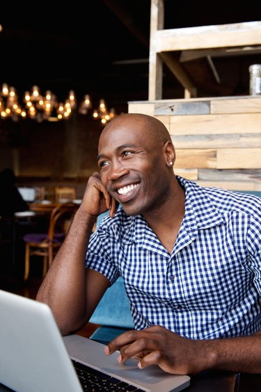 Happy african man sitting at a cafe with laptop