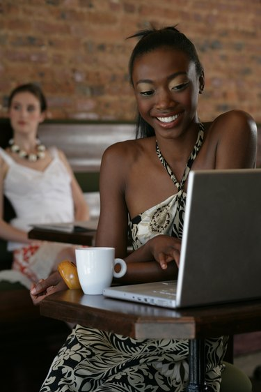Young African-American woman using laptop in cafe.