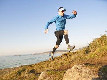 Man practicing trail running in a coastal landscape