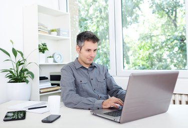 Young man at office desk, working on laptop