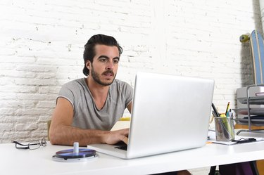 hipster student or businessman working with laptop computer at office