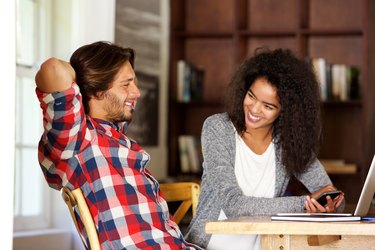 Man and woman sitting at table with laptop and phone